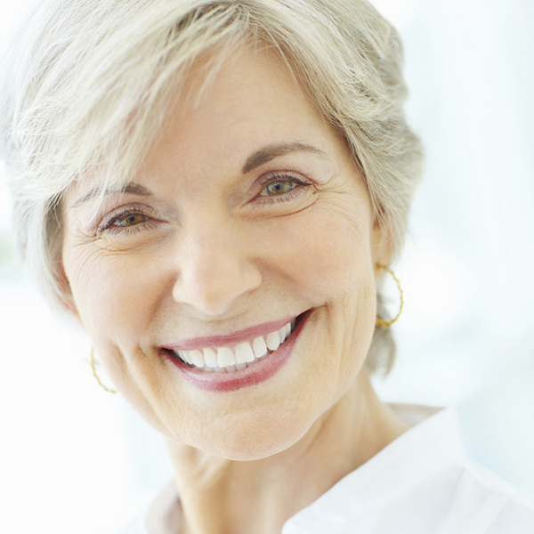 Detail shot of a happy mature woman giving you a cute smile